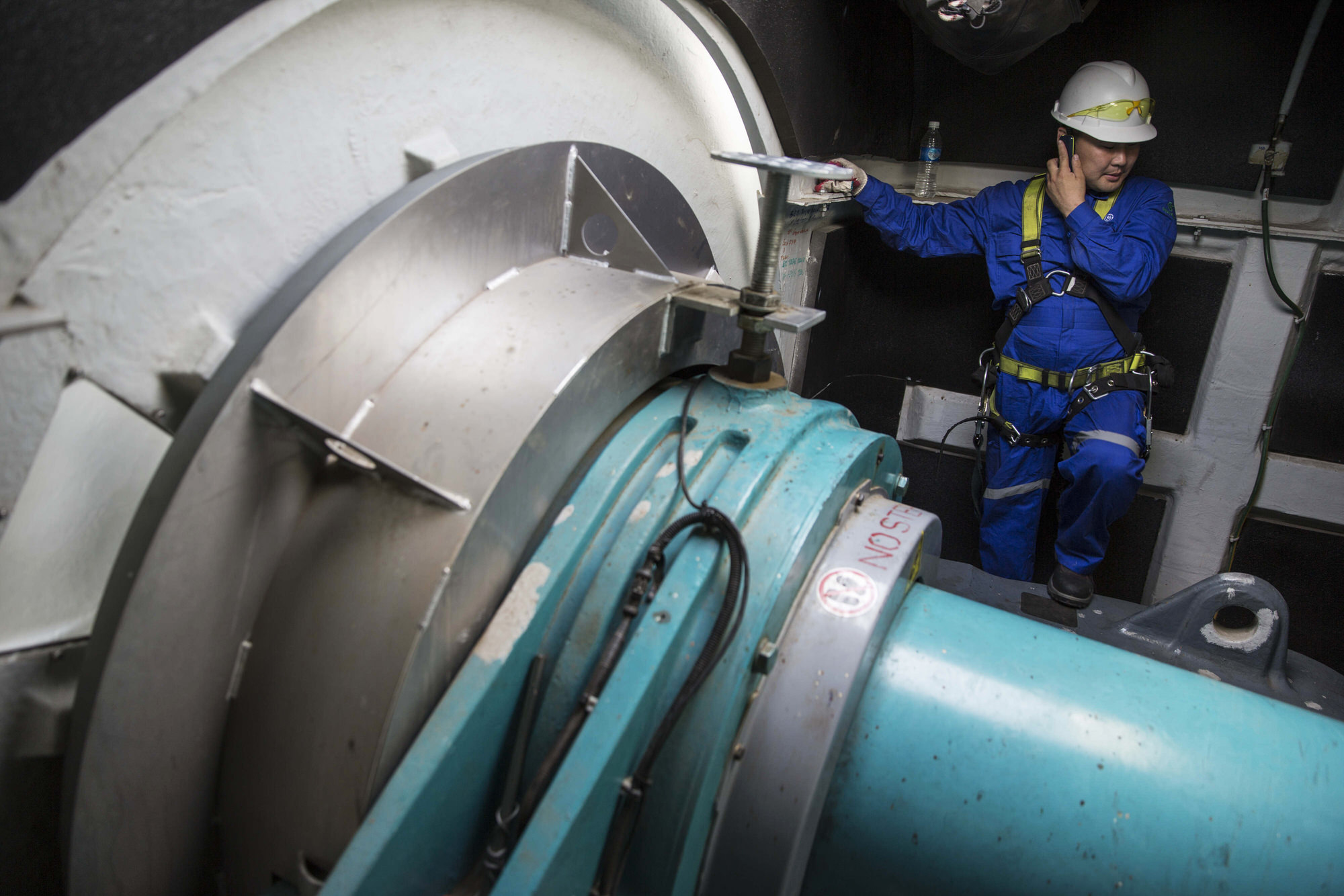 An engineer performs maintenance work inside the nacelle of a General Electric Co. (GE) wind turbine at the Salkhit Wind Farm operated by Clean Energy LLC, a unit of Newcom Group, stand on the steppe in Khongor district of Darkhan-Uul Province, Mongolia, on Thursday, July 21, 2016. Newcom completed the 50-megawatt Salkhit project in 2013 at a cost of $120 million, marking the first time in 30 years that a new power plant was connected to Mongolia's central grid. Photographer: Taylor Weidman/Bloomberg