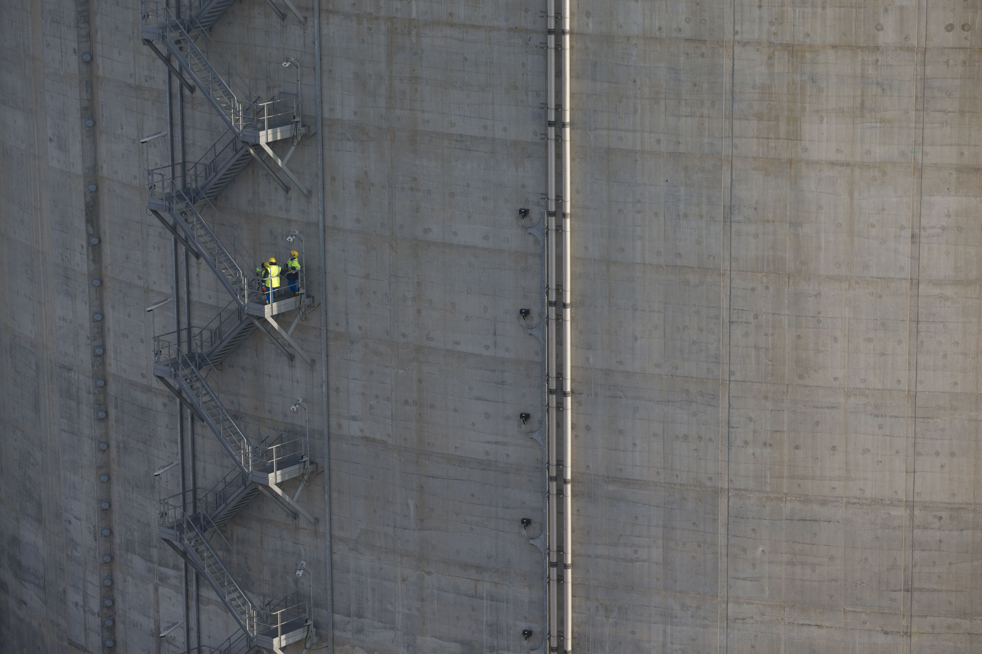 Workers stand on a storage silo staircase as construction work continues at the liquid natural gas (LNG) terminal, a unit of Electricite de France (EDF) SA, in Dunkirk, France, on Tuesday, March 15, 2016. The terminal, near the Belgian border, is poised to go into operation as LNG tankers head to Europe after demand waned elsewhere. Photographer: Jasper Juinen/Bloomberg