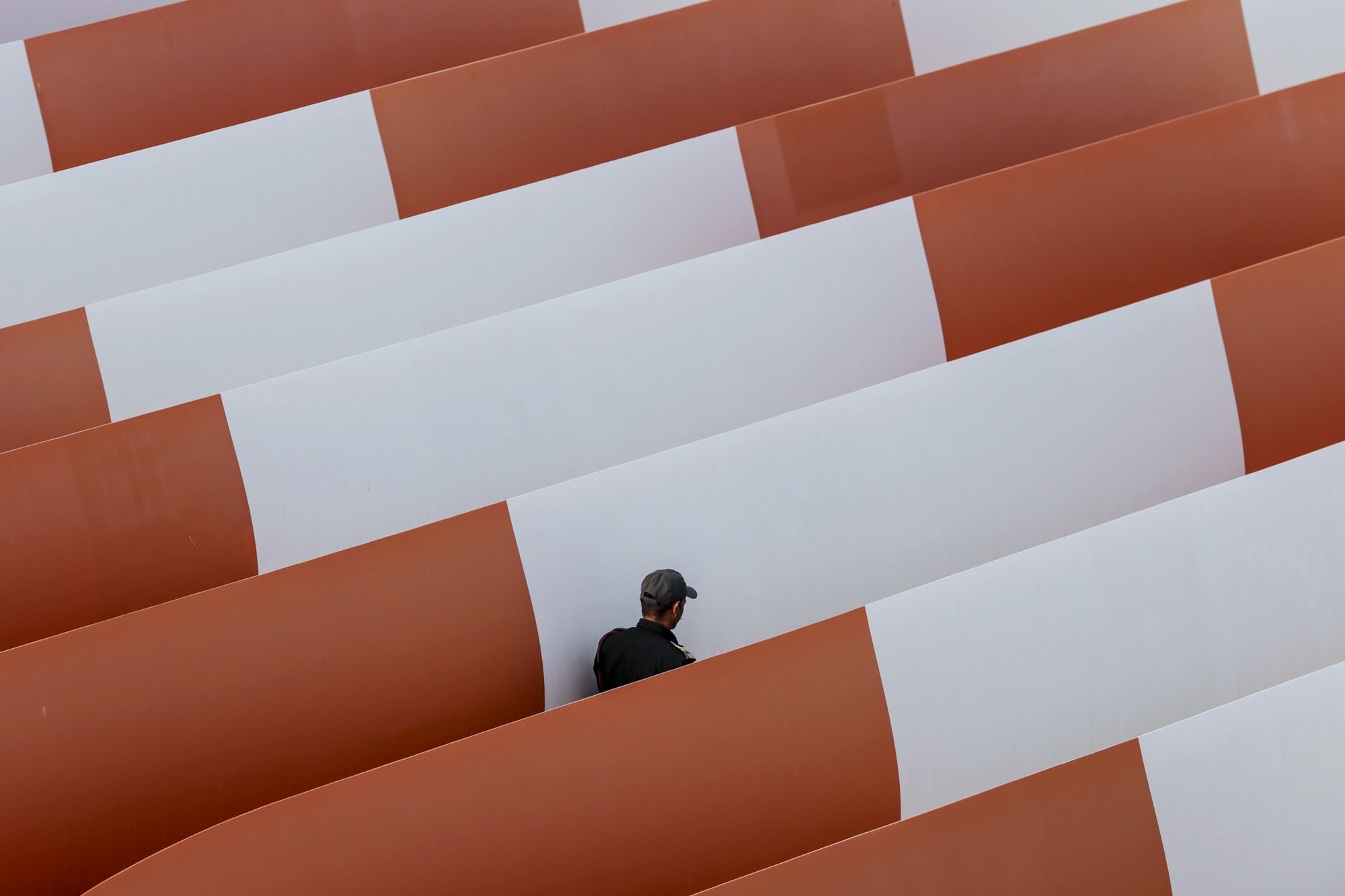 Bloomberg's Best Photos 2014: A security guard walks between finished turbine blades sitting in an outdoor storage area at the Suzlon Energy Ltd. rotor blade manufacturing plant in Bhuj, India, on Friday, March 28, 2014. Suzlon, the fifth-largest turbine maker, has won approval from shareholders to re-appoint founder Tulsi Tanti as managing director. Photographer: Dhiraj Singh/Bloomberg