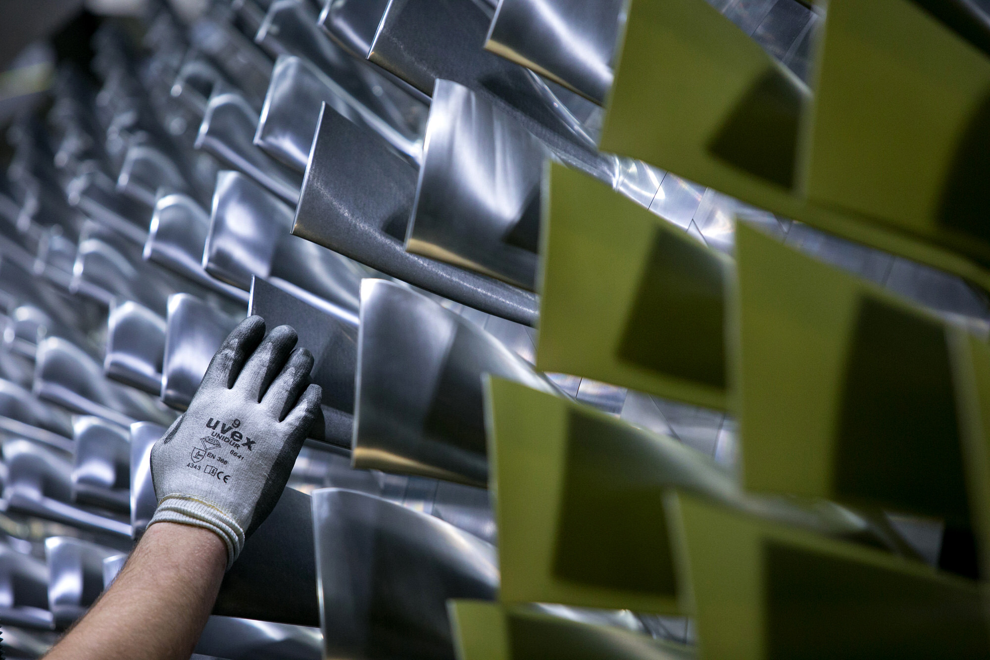 An employee inspects the blades on a H-class turbine on the assembly line of Siemens AG's gas turbine factory in Berlin, Germany, on Tuesday, Feb. 2, 2016. Siemens, Europe's largest engineering company, criticized the U.K. government for creating uncertainty in the energy industry, saying it hampers investment in gas plants, wind farms and factories. Photographer: Krisztian Bocsi/Bloomberg