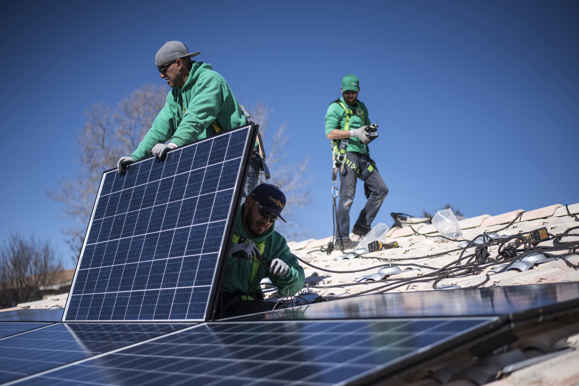 Workers secure solar panels to a rooftop during a SolarCity Corp. residential installation in Albuquerque, New Mexico, U.S., on Monday, Feb. 8, 2016. SolarCity is scheduled to release earnings figures on February 9. Photographer: Sergio Flores/Bloomberg