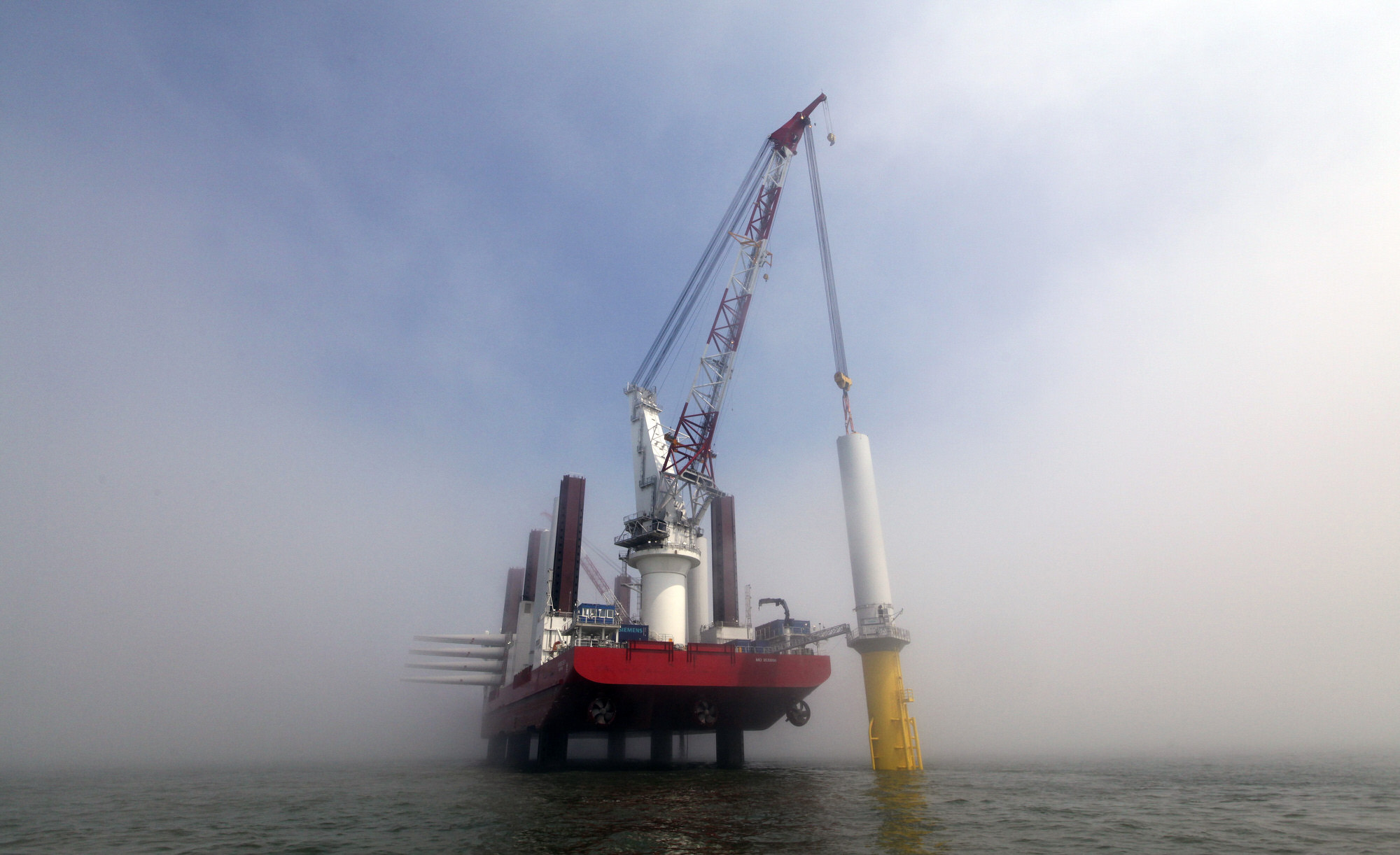 The MPI Discovery, a jack-up vessel operated by MPI Offshore, lowers a tower section at the London Array project, the worldÕs largest consented wind farm, a partnership between Dong Energy A/S, E.ON AG and Abu Dhabi-based Masdar in the Thames Estuary, U.K., on Thursday, May 24, 2012. Britain, which has more than 1,500 megawatts of offshore wind, plans to increase capacity to 18,000 megawatts by 2020 in a bid to meet rising energy demand without adding emissions. Photographer: Chris Ratcliffe/Bloomberg