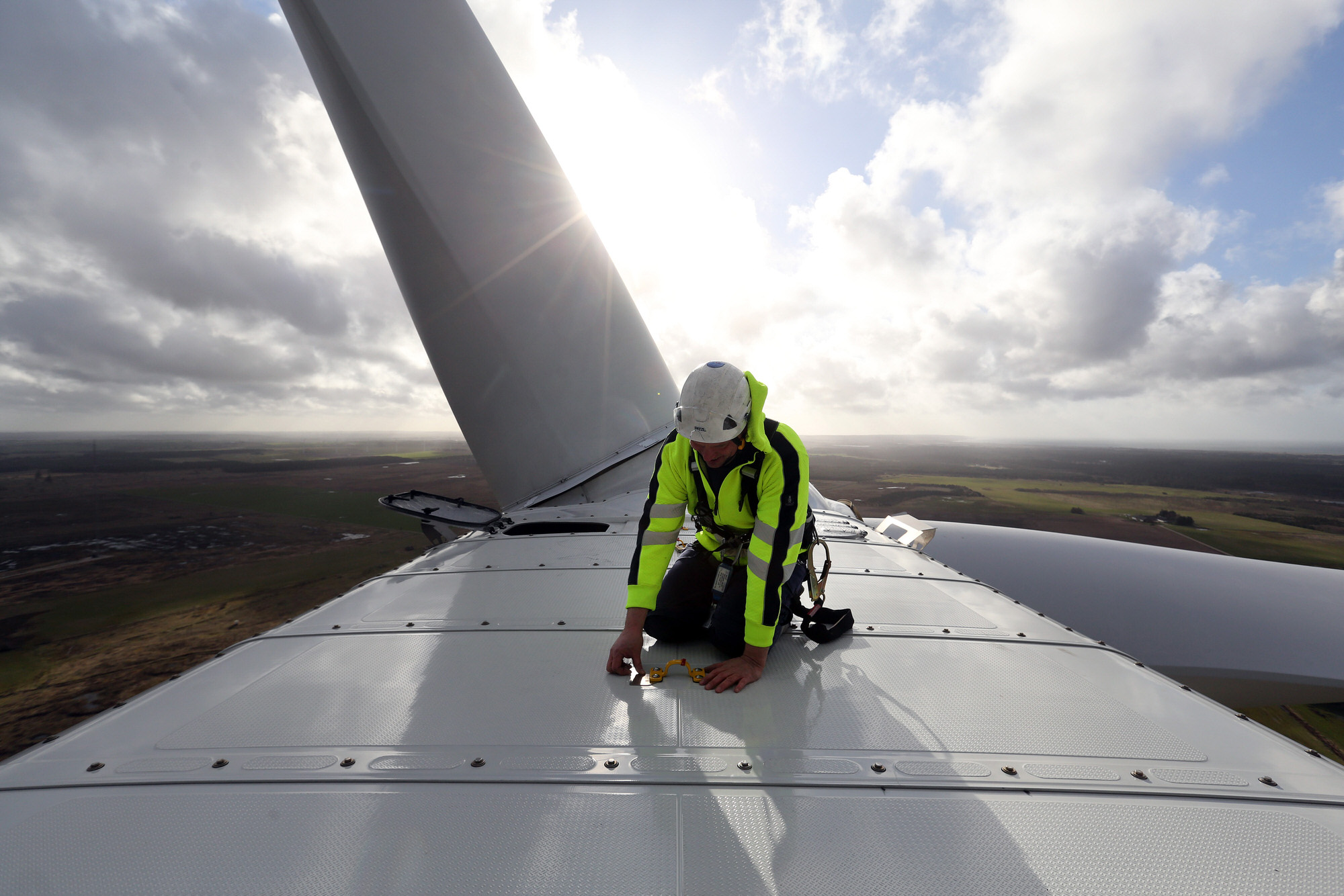"An employee checks a cable on the nacelle of a Vestas A/S V136 wind turbine during operational testing at the Danish National Test Center for Large Wind Turbines in Osterild, Denmark, on Monday, April 18, 2016. ""The doubling of turbine size this decade will allow wind farms in 2020 to use half the number of turbines compared to 2010,"" said Tom Harries, an industry analyst at Bloomberg New Energy Finance. Photographer: Chris Ratcliffe/Bloomberg"