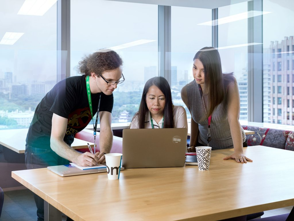 Department team huddled around laptop
