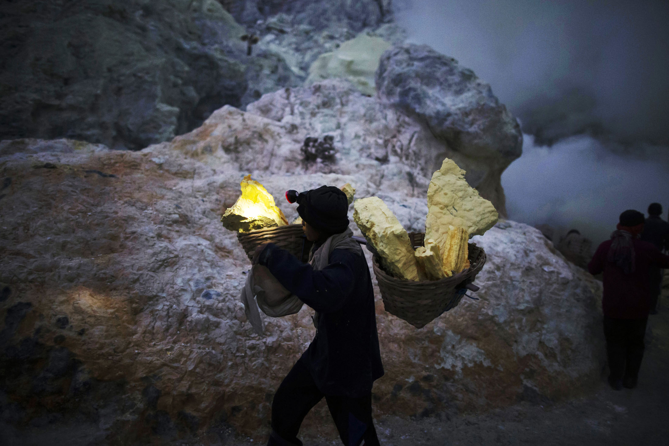 Resultado de imagem para Miners extract the sulfur rock, which is formed after the blue flames