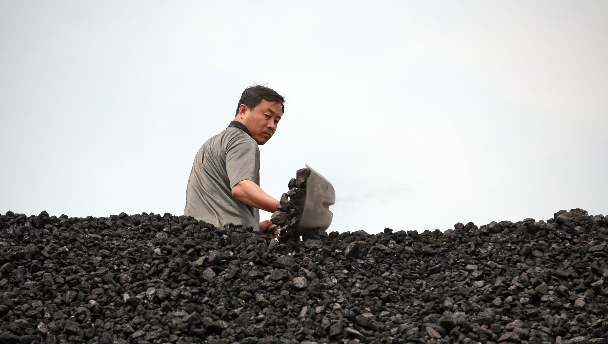 A coal yard worker shovels a load of coal on to the back of a truck in Ningan in Heilongjiang Province July 5, 2006. China saw sharp growth in energy consumption this year. According to statistics, in the first four months, China's coal consumption rose by 13.8 percent over the same period of last year, coke, 11 percent and electricity, 12.5 percent.